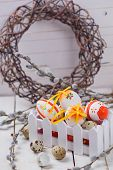stock photo of willow  - Colorful easter eggs in box willow branches on wooden background - JPG