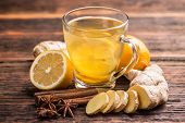 stock photo of ginger  - Cup of ginger tea with lemon on wooden table - JPG