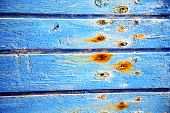 stock photo of nail paint  - stripped paint in the blue wood door and rusty nail