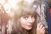 stock photo of thrift store  - portrait of a beautiful teenage girl and her wardrobe with bokeh - JPG