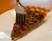 picture of pecan  - Fork plunging into a piece of pecan pie on a white plate - JPG