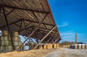 foto of canopy roof  - Long roof protecting straw bales and fire wood - JPG