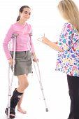 happy woman on crutches talking to nurse