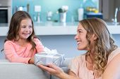 foto of daughter  - Daughter surprising mother with gift at home in the living room - JPG