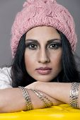 pic of pakistani  - portrait of a young indian pakistani woman wearing a pink knitted winter cap and posing for the camera during a model shoot - JPG