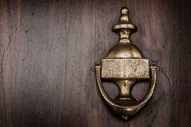 stock photo of in front  - A copper door knocker on a wooden front door - JPG