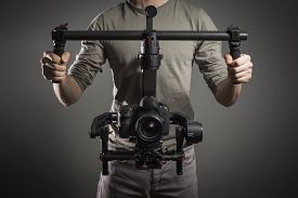 picture of stability  - Man with filmmaking digital camera stabilization equipment - JPG