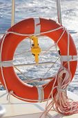picture of passenger ship  - Orange colored lifebelt and rope hang on a white banister a passenger ship - JPG
