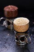 picture of quinoa  - White raw quinoa in a glass cup red quinoa on back dark background selective focus - JPG