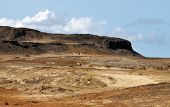 foto of plateau  - Dry landscape filled with sand dunes and dirt under the plateau which is the highest point in the islet of Djeu in Cabo Verde - JPG