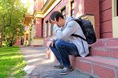 foto of knapsack  - Sad Young Man with Knapsack on the Porch of the House - JPG
