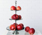 pic of serving tray  - Tasty ripe apples on serving tray on brick wall background - JPG