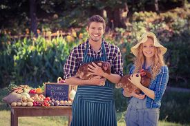 picture of stall  - Happy farmers standing at their stall and holding chicken on a sunny day - JPG