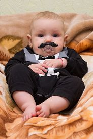 stock photo of pacifier  - Toddler with pacifier is lying on plaid mustache - JPG