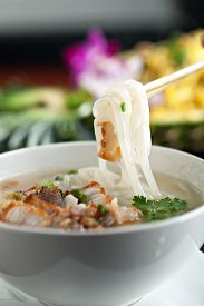 picture of crispy rice  - Closeup of a person eating Thai style crispy pork rice noodle soup from a bowl with chopsticks. Pineapple fried rice in the background. ** Note: Soft Focus at 100%, best at smaller sizes - JPG