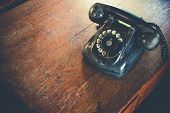 Black Antique Vintage Analog Telephone Dialing Or Scrolling Phone On Wooden Table. Contact Us Concep poster