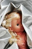 Small doll wrapped up in a silver fabric