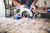 Carpenter Using Circular Saw For Cutting Wooden Boards. Construction Details Of Male Worker Or Handy poster