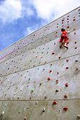 Esforço do jovem em uma parede de escalada para chegar ao topo.