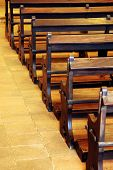 Row of wooden pews inside of a church
