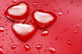 Three melting heart-shaped ice cubes over a red background