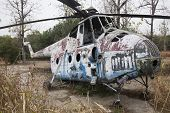 Wreck of an Old Soviet military chopper in a garden outdoor.