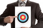 Businessman holding a target and pointing at the bullseye, copy space above for heading