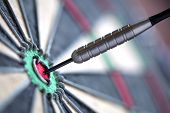 picture of differential  - Dart in bulls eye of dartboard with shallow depth of field concept for hitting target - JPG