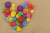 Colorful wooden buttons arranged in heart shape on handwoven cotton fabric.