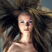 Portrait of a beautiful girl with flying blond hair. Attractive woman with a charmed look