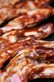 Ribs covered with barbecue sauce sizzling on the BBQ