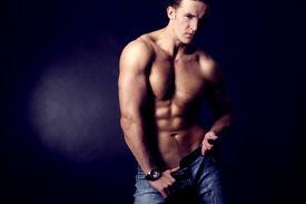 stock photo of body builder  - Beautiful young man posing on dark background - JPG