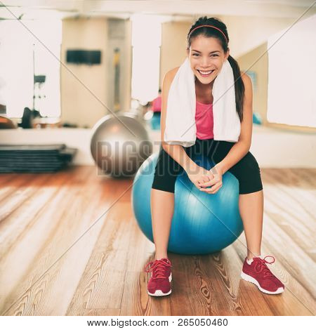 poster of Fitness girl exercising happy in gym resting on pilates exercise ball after training class. Asian wo