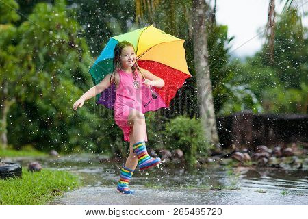 poster of Kid With Umbrella Playing In Summer Rain.