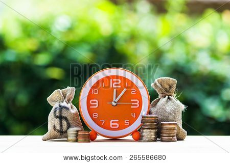 poster of Money Savings, Investment, Growing Concept : Stacking Growing Coins, Money Bags And Orange Clock On