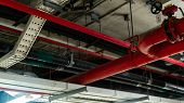 Fire Sprinkler System With Red Pipes Hanging From Ceiling Inside Building. Fire Suppression. Fire Pr poster