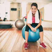 Fitness girl exercising happy in gym resting on pilates exercise ball after training class. Asian wo poster