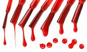 Set Of Red Nail Polish Brushes And Drops Isolated On White