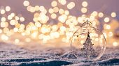 Christmas glass ball with tree in it on winter background. Snow and christmas lights. poster