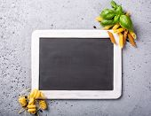 Black Chalkboard With Italian Pasta Whole Grain Penne, Trottole And Basil Leaves On Gray Concrete Ta poster