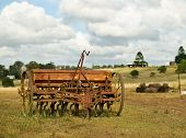 Old Farm Machinery Plough Tiller With Cloudy Sky