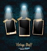 Antique distressed photoframes with vintage seamless wallpaper background and two spotlights.