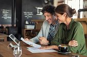 Portrait of mature business man and casual businesswoman sitting in cafe and discussing sales graph. poster