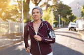 Senior woman jogging on street during late afternoon. Healthy mature woman running while listening t poster