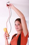 Female electrician fixing ceiling lighting
