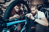 Guy And Bike Mechanic Repairs Bicycle In Workshop. Closeup Portrait Of Young Caucasian Man Wearing A poster