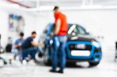 Blurred Abstract Image Of Man Worker With Car In A Body Shop. Blur Car Auto Service. Car Bokeh. Blur poster