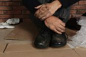 Poor Man Wearing Old Dirty Shoes Sitting On Floor poster