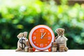 Money Savings, Investment, Growing Concept : Stacking Growing Coins, Money Bags And Orange Clock On  poster