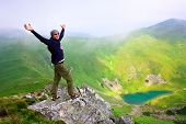 Beautiful mountains landscape with lake  in Carpathian mountains and man on the top